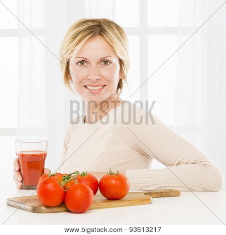 Forty years woman  drinking tomatoes juice