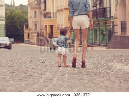 Young Mother Strolling With Tiny Daughter