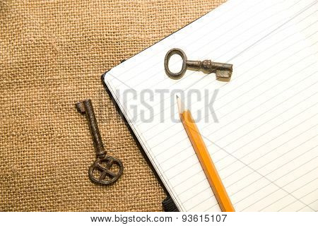 Opened Notebook, Keys And Pencil On The Old Tissue