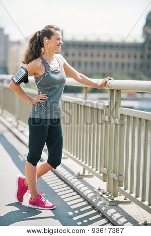 Smiling Woman In Workout Gear Standing On A Bridge