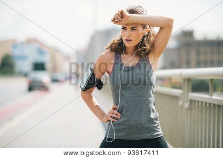 Woman Jogger Taking A Break On Bridge While Wiping Forehead