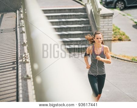 Woman Jogger In The Zone Running Along Sidewalk