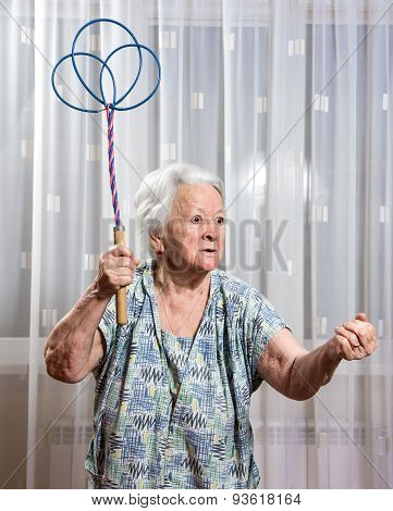 Old Angry Woman Threatening With A Carpet Beater