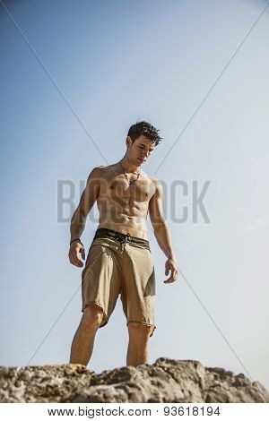 Muscular young man shirtless against the sky