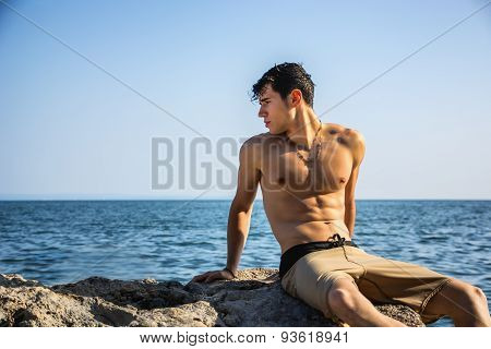 Young shirtless athletic man crouching in water by ocean shore