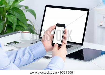 Male Hands Using Smartphone Mockup At The Office Desk With An Open Laptop Mockup