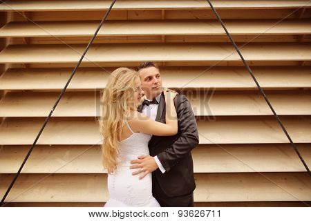 Bride And Groom Posing Against Striped Wall