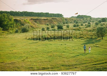 Lovely Couple Play With Sky Air Kite At Green Meadow