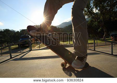 closeup of young woman skateboarding at skatepark