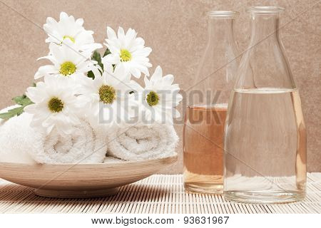 bottles with fragrance beside white towels and bunch of margarite flowers