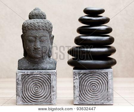 buddha statue beside pile of basalt massage stones