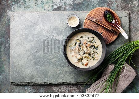 Creamy Soup With Eel In Black Iron Pot On Stone Slate Background