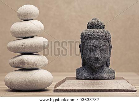 buddha statue beside stack of pebble stones