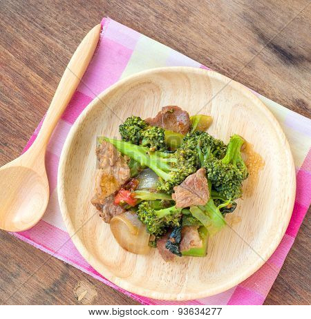 Fried Broccoli And Pork In Wood Plate Placed On A Wooden Table.