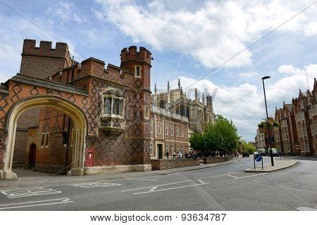 WINDSOR, ENGLAND - JUNE 11, 2015: Archway Entrance to Historic Eton College, a Boarding School for Boys, with Curved Road and Blue Sky, Berkshire, England on June 11, 2015