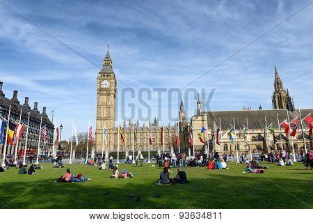 LONDON, ENGLAND - JUNE 18, 2015:  Crowd of people relaxing at the Houses of Parliament, London lounging on the green lawns in front of the Big Ben clock tower,  view on a sunny day on June 18, 2015