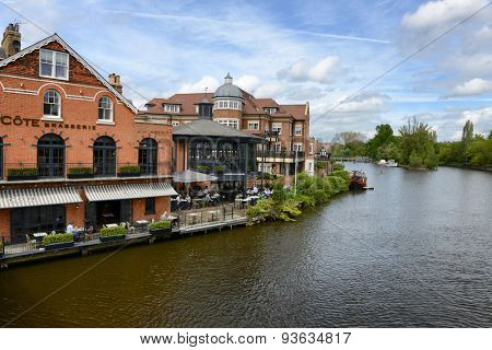 WINDSOR, ENGLAND - JUNE 11, 2015: Waterfront buildings along the bank of the River Thames in Windsor, Berkshire, UK in a scenic landscape view on June 11, 2015