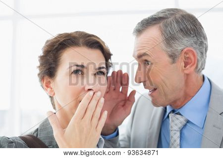 Businessman whispering something to his colleague in an office