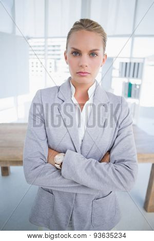 Unhappy businesswoman looking at camera with arms crossed in her office
