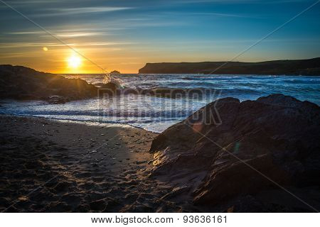 Setting sun at Polzeath beach, a noted surfers beach in Cornwall, UK