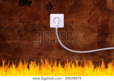 rusty iron wall with an electrical outlet and fire. Danger