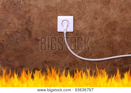 grunge wall with an electrical outlet and fire. Danger