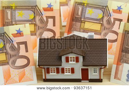 Little model house with banknotes in the background