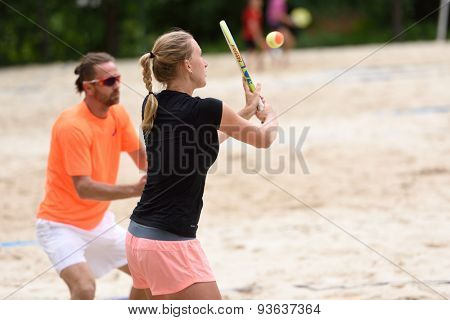 MOSCOW, RUSSIA - MAY 31, 2015: Irina Glimakova and Sergey Kuptsov in the match of Russian beach tennis championship. 120 adults and 28 young athletes compete in the tournament
