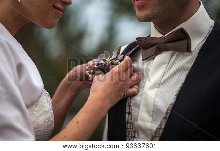woman adjusting boutonniere