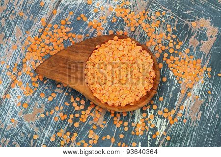 Uncooked red lentils in bamboo dish on rustic surface