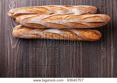 Three Fresh French Baguette On Gray Wooden Background