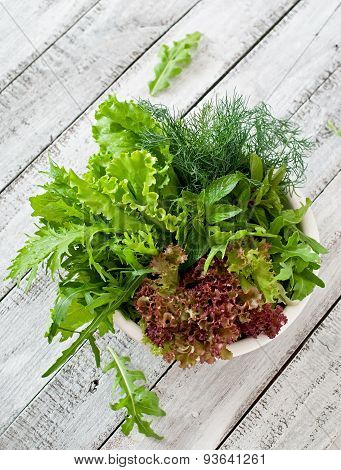 Variety fresh organic herbs (lettuce, arugula, dill, mint, red lettuce) on wooden background in rust