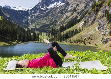Woman Doing Eye Of The Needle Pose Outdoors