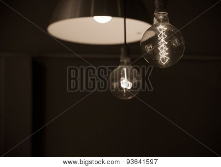 Hanged Lamps  Focused On Light Bulb In Dark Room  In Sepia Tone
