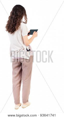 back view of standing young beautiful  girl with tablet computer in hands of. girl  watching. Rear view people collection.  Isolated over white background. Girl in brown trousers with reading tablet