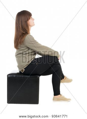 back view young beautiful woman sitting. girl watching. Rear view people collection.  backside view of person. Isolated over white background. Pretty teenage girl sitting on black ottoman legs crossed