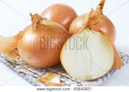 close up of raw onions on grey checkered dishtowel