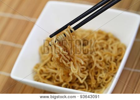 Chinese noodles in bowl and chopsticks on bamboo mat