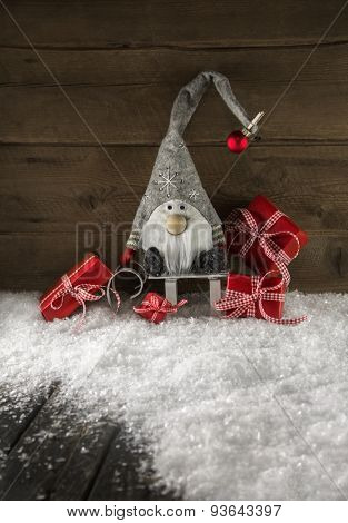 Funny imp on wooden background with red christmas presents.