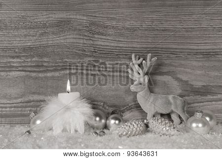 Grey, white silver christmas decoration with one burning candle on wooden background.