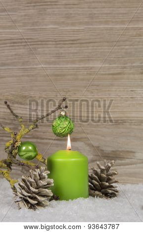 One burning advent candle on an empty wooden background with snow and other decoration.