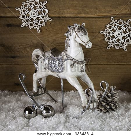 Old rocking horse in white and silver for christmas decoration.