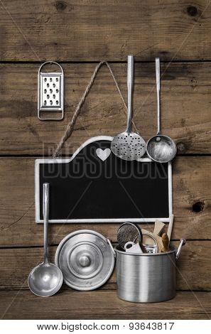 Wooden vintage kitchen background with old kitchenware, blackboard and spoons for cooking fans.