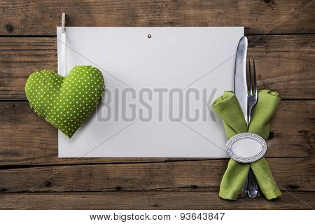 Menu card with a green heart and white polka dots plus cutlery and napkin for a background.