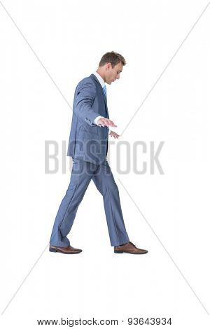 Businessman walking in equilibrium on white background