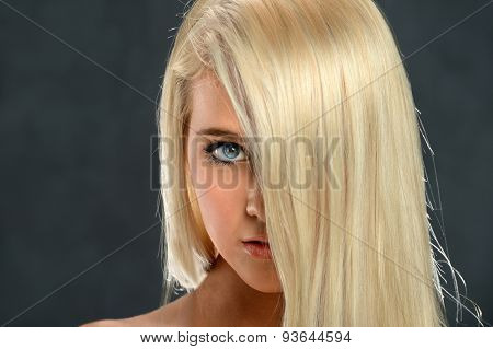 Portrait of beautiful young teen girl with blond hair covering part of face