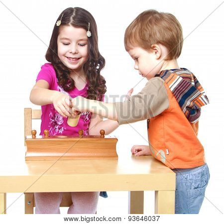 Brother and sister in Montessori kindergarten work with the puzz