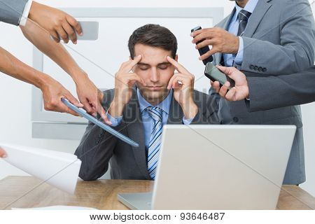 Worried businessman with head in hands sitting at the office