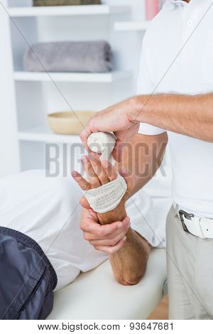 Doctor bandaging his patient hand in medical office