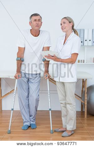 Man with crutch speaking with his doctor in medical office